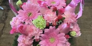 手つきのバスケットにピンクのガーベラ、ピンクのバラ、グリーンとピンクのスプレーカーネーション、ヒペリカム